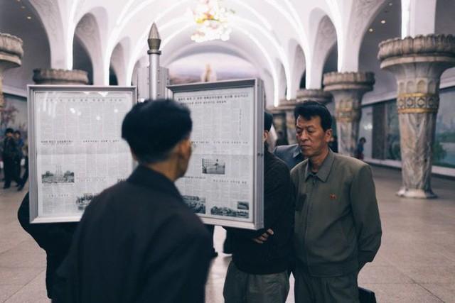 Người dân đọc báo dưới sân ga. Ảnh: CNN/Elaine Li