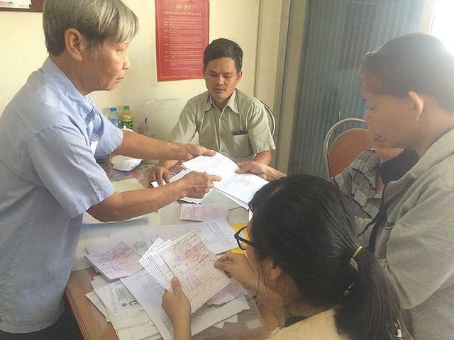 Người dân đang đối chiếu hồ sơ, chứng từ, hóa đơn… liên quan đến khoản tiền gửi tại Quỹ tín dụng nhân dân Thái Bình ở Đồng Nai. Ảnh: VŨ HỘI