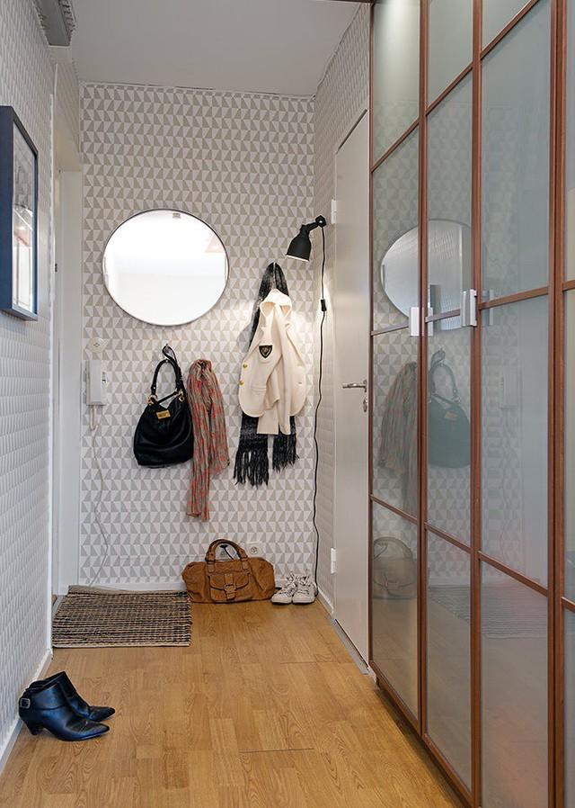 Từ cửa bước vào nhà là một hành lang nhỏ. Nơi đây được thiết kế nhẹ nhàng với bức tường được gián giấy hình lập thể tạo chiều sâu cho không gian.