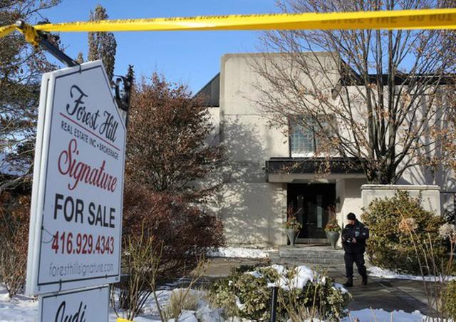 Nhân viên khám nghiệm pháp y đứng bên ngoài ngôi nhà của ông Sherman hôm 16-12. Ảnh: REUTERS