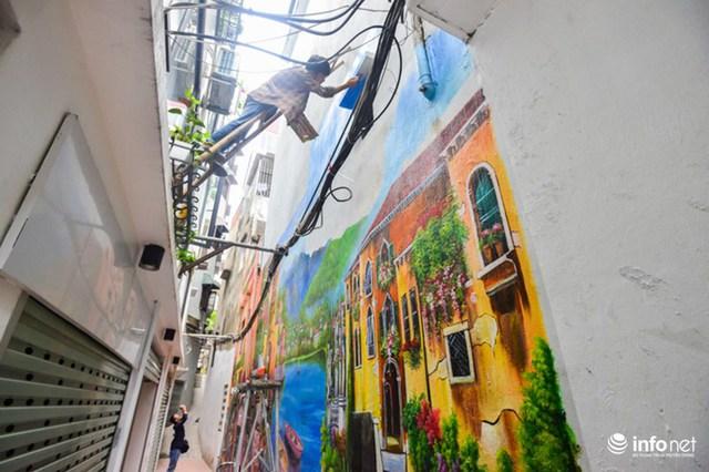 Bức tranh cao tới 5m nên các thành viên nhóm vẽ phải bắc thang qua lan can tầng 2 để hoàn thiện những công đoạn cuối cùng.