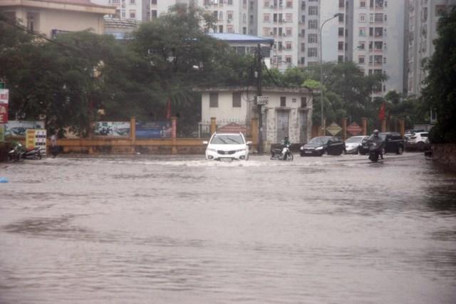 Trước đường tiểu học Nam Trung Yên, các phương tiện xe máy phải cho xe lên vỉa hẻ, tránh nước ngập sâu