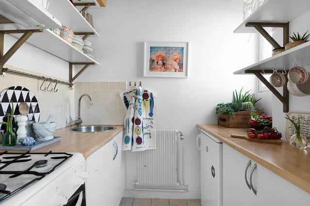 Một nhà bếp nhỏ được kiến trúc kín đáo ngay cạnh bàn ăn. Bằng cách chọn lọc kệ mở thay vì các chiếc tủ bếp như bình thường, nhà bếp trông rộng rãi hơn và gây ấn tượng nhờ không gian lưu trữ không nhỏ mà chúng tạo ra.