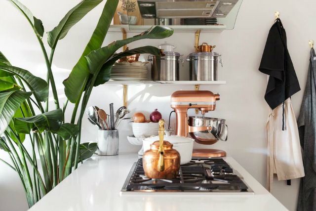 Ngay cạnh không gian tiếp khách là khu vực bếp và bàn ăn. Trên nên trắng chủ đạo của tường, trần nhà góc bếp nhỏ được thiết kế vô cùng đặc biệt với điểm nhấn là những món nội thất màu đồng sang trọng.