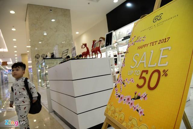 Các cửa hàng vẫn trưng bày và trang trí các biển hiệu giảm giá sản phẩm từ trước Tết.