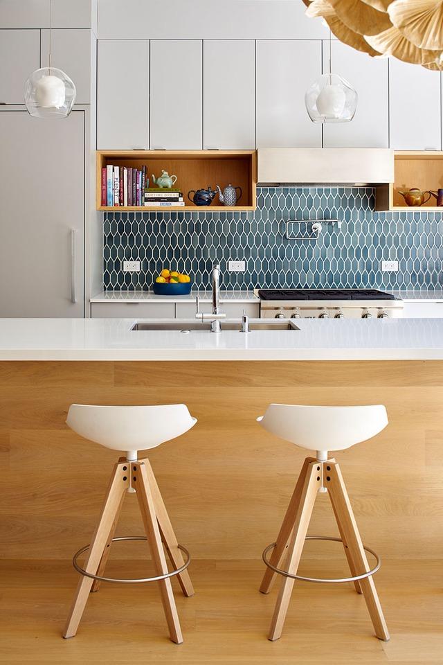 Bức tường bếp được ốp gạch màu xanh nổi bật trên nên trắng của gian bếp.