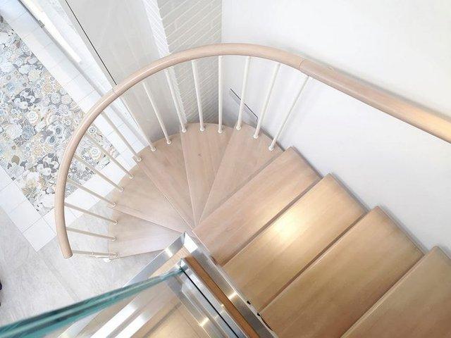 Cầu thang gỗ uốn lượn dẫn lên khu vực nghỉ ngơi của chủ nhà.