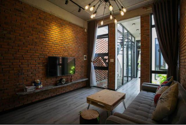 Phòng khách tuyệt đẹp với chiếc ghế sofa dài cùng bàn trà gỗ lạ mắt. Chiếc ti vi màn hình rộng cùng với giá để đồ được gắn cố định vào tường giúp tiết kiệm diện tích và gọn gàng.