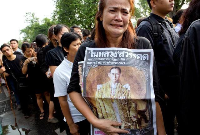 Một người phụ nữ Thái Lan khóc nấc khi đang ôm tấm chân dung của nhà vua Thái Lan. Cô là một trong hàng trăm, hàng nghìn người dân đang đứng chờ để được vào viếng vua Bhumibol. Ảnh: AP.