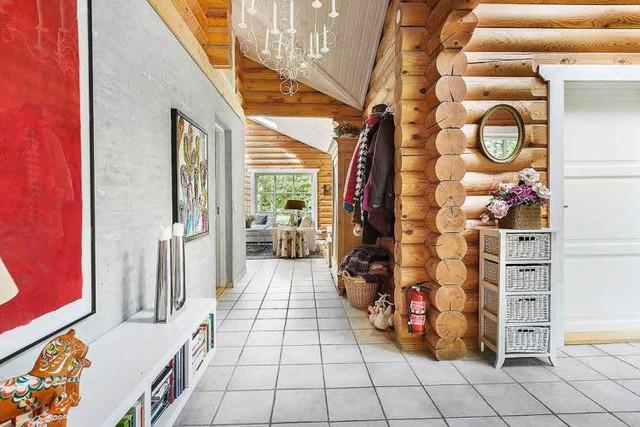 Những bức tường gỗ nguyên khối hình tròn xuyên suốt ngôi nhà với tông màu sáng tạo cảm giác vô cùng ấm cúng và gần gũi với thiên nhiên.
