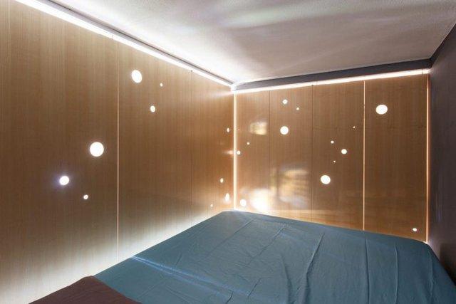 Không gian nghỉ ngơi lung linh với ánh sáng điện tỏa ra từ khe cửa và những lỗ tròn to nhỏ giúp thông khí của cánh cửa gấp.