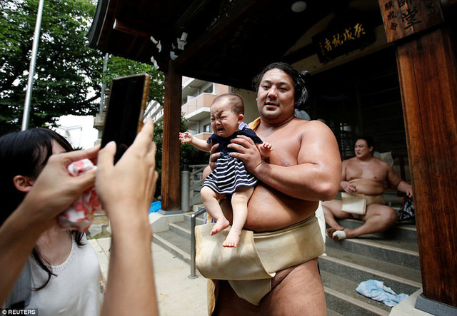 Võ sĩ sumo Kyokutaisei chụp hình cùng một em bé trước cửa đền.