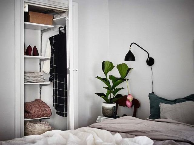Vẫn trung thành với gam màu trắng chủ đạo, điểm nhấn đặc biệt của phòng ngủ chính là chậu cây hoa tuyệt đẹp ngay đầu giường. Để tạo giấc ngủ sâu ga gối trên giường được chủ nhà chọn tông màu trầm.