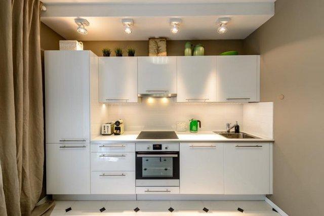 Một hệ thống tủ kệ khép kín nơi bếp ăn làm tăng không gian lưu trữ. Một vài chậu cây cảnh cũng góp mặt nhằm đưa sức sống của thiên nhiên vào trong nhà bếp.
