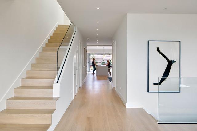 Toàn bộ sàn nhà và cầu thang được ốp gỗ sáng màu.