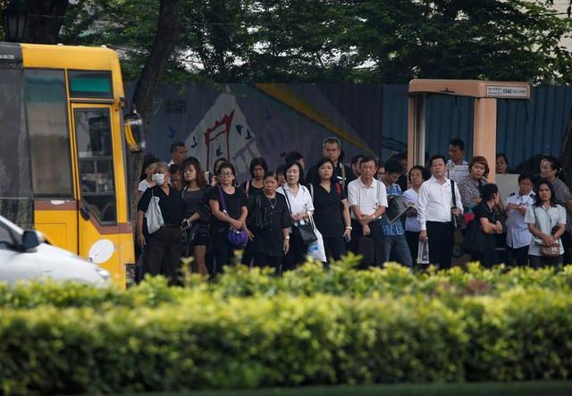 Một số người chưa thể tới viếng Quốc vương cũng cùng nhau mặc áo đen trong khi chờ xe buýt. Ảnh: Reuters.