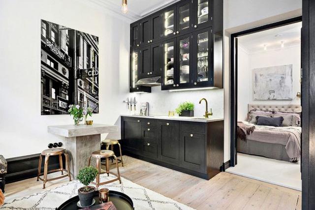 Một không gian nhà bếp gọn gàng, ngăn nắp được tạo ra với một diện tích khiêm tốn ngay bên cạnh phòng khách. Góc nhỏ này được bài trí khéo léo với hệ thống tủ kệ khép kín và những chậu cây xanh nhỏ xinh. Khu bàn ăn lạ mắt cùng những chiếc ghế có thể dễ dàng thu gọn lại khi không sử dụng.