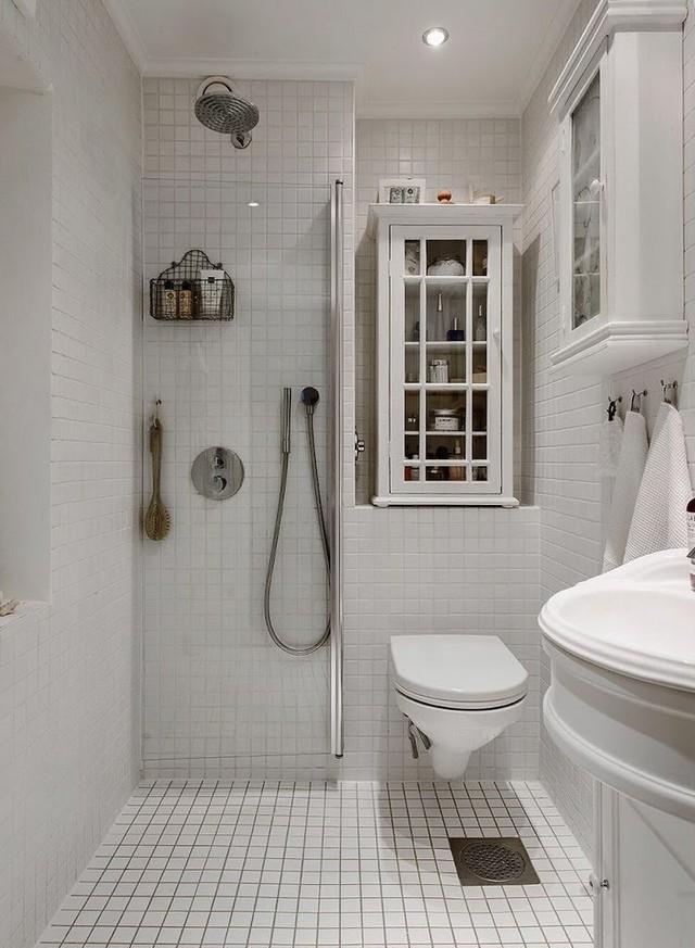 Được bố trí ở một khu vực nhỏ nơi góc nhà méo mó nhưng không gian nhà tắm được thiết kế khá ấn tượng và vô cùng gọn gàng ngăn nắp với giá treo và hệ kệ để đồ dùng.