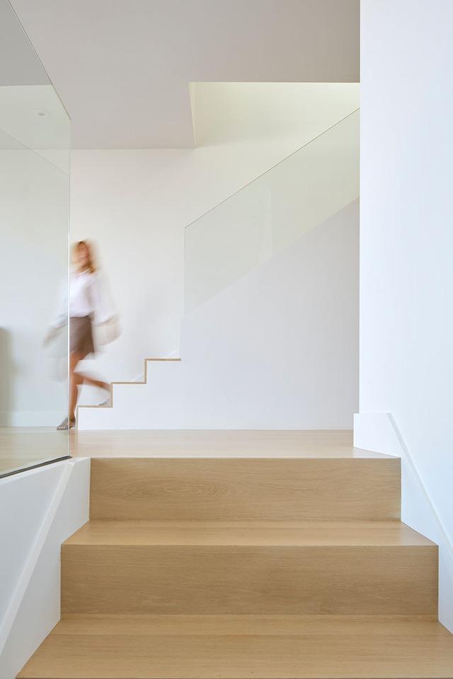 Cầu thang dẫn lên tầng 2 rộng được thiết kế với lan can bằng kính trong suốt.