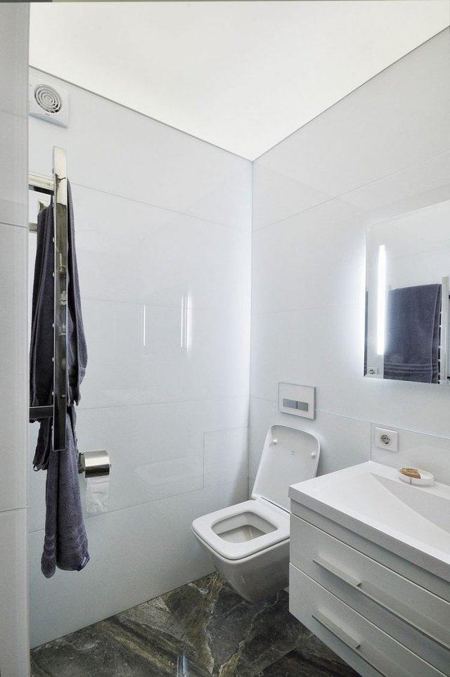 Nhà vệ sinh sáng bóng được kiến trúc kín đáo cạnh lối vào nhà.