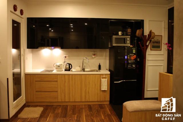 Góc bếp nhỏ xinh được thiết kế khéo léo tiết kiệm diện tích chạy dọc bức tường nhà. Chiếc tủ lạnh và tủ bếp màu đen hình chữ L như một điểm chấm phá tạo nét độc đáo cho góc nấu ăn.