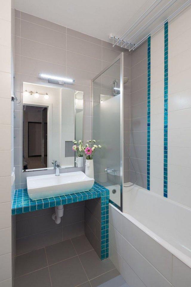 Sự kết hợp hài hòa giữa màu xanh ngọc làm và màu nâu của sàn nhà tắm khiến không gian càng trở nên thoáng sạch hơn.
