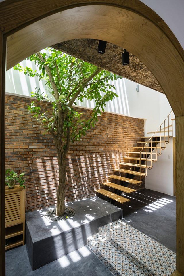 Một chiếc cầu thang với thiết kế đơn giản, lạ mắt nằm ở ngoài sân dẫn lên khu vực riêng ở tầng 2.