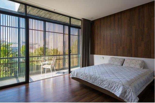 Phòng ngủ lớn với bức tường kính rộng mở và một ban công hướng tầm nhìn ra biển tuyệt đẹp.