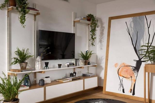 Góc nhỏ được bố trí đơn giản với bộ sofa nâu cùng bàn trà 3 chân gọn gàng. Phía đối diện là vị trí dành cho tivi và hệ tủ kệ mở tuyệt đẹp.