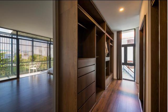 Phía sau giường ngủ là phòng tắm và hệ tủ gỗ đựng đồ tiện dụng.
