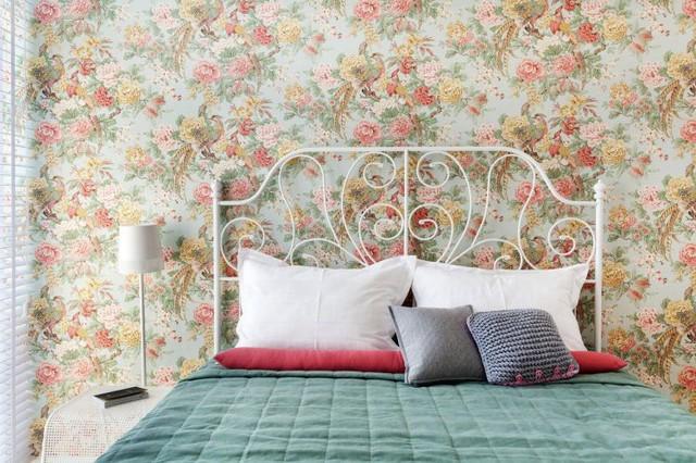Bức tường nơi đầu giường ngủ được sử dụng giấy dán tường họa tiết hoa lá nhiều màu sắc.