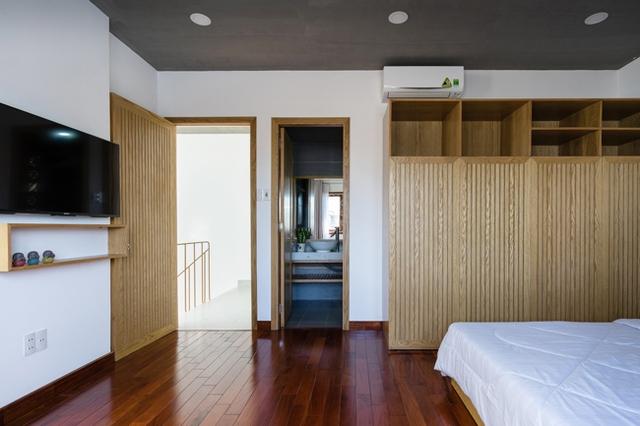 Không gian phòng ngủ ấm cúng với nền nhà ốp gỗ màu cánh dán.