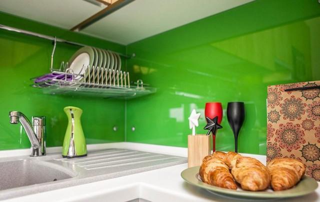 Màu xanh đậm của bức tường nơi góc bếp và những món nội thất nhỏ xinh giúp không gian nấu ăn thêm dịu mát.