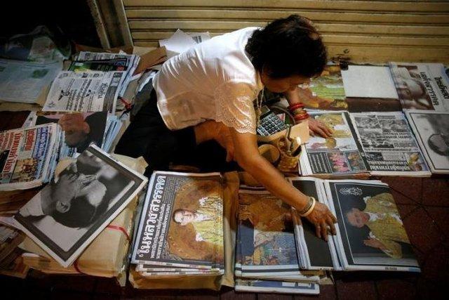 Một sạp báo tại thành phố Bangkok, Thái Lan tràn ngập thông tin về sự ra đi của Quốc vương trên trang nhất. Người bán hàng đang cẩn thận xếp từng tờ báo lại ngay ngắn.