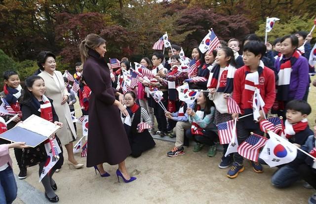 Đệ nhất phu nhân Mỹ Melania Trump và phu nhân Tổng thống Hàn Quốc Kim Jung-sook được các em bé chào đón tại Nhà Xanh, ở Seoul hôm 7/11.