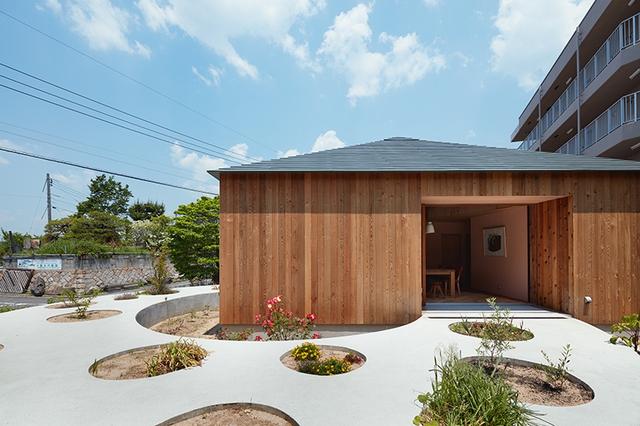 Ngôi nhà nhỏ nằm trong một khu dân cư yên tĩnh. Phần lớn cấu trúc được làm từ gỗ sáng màu.
