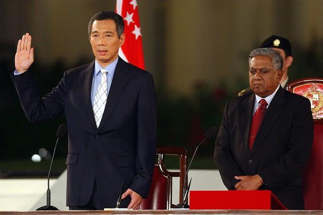 Về nước, ông nhập ngũ rồi trở thành nghị sĩ năm 1984, chính thức bắt đầu sự nghiệp chính trị. Ông từng giữ các vị trí bộ trưởng Thương mại và Công nghiệp, thứ trưởng Quốc phòng và phó thủ tướng trước khi trở thành thủ tướng thứ 3 trong lịch sử Singapore. Trong ảnh, ông Lý Hiển Long tuyên thệ nhậm chức thủ tướng vào ngày 12/8/2004. Ảnh: Straits Times.