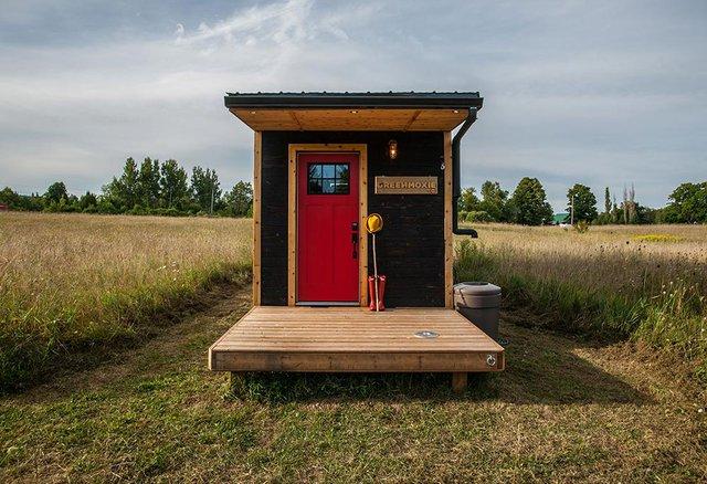 Vật liệu làm nên ngôi nhà này đó là gỗ tuyết tùng. Mặt tiền nhà xinh xắn với khoảng hiên nhà rộng và chiếc cửa ra vào màu đỏ nổi bật trên nền đen của gỗ.