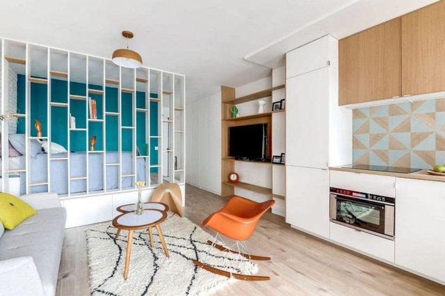 Phòng khách và bếp được ưu tiên bố trí chung một không gian thoáng sáng nhất cạnh ban công. Nơi đây được ngăn cách với không gian bên ngoài bằng một hệ thống cửa kính cao sát trần để tận dụng tối đa nguồn sáng tự nhiên.