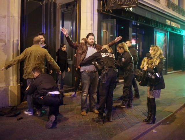 Một người đi đường bị lục soát. Cảnh sát nói nghi phạm đã chạy trốn trước khi bị bắn hạ. Ảnh: Getty.