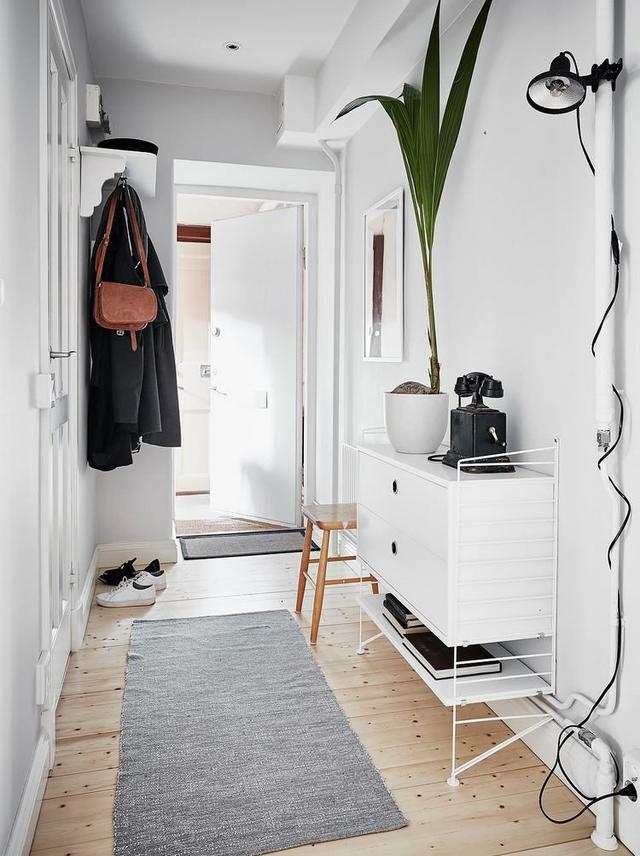 Lối vào nhà được bài trí đơn giản với móc treo và tủ để đồ.