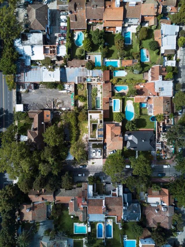 Trên dải đất khá dài, công trình được thiết kế với phía trước là nơi để xe và sân sau là cả một khu vườn dài và bể bơi xanh biếc.