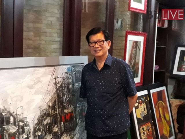 Ông Đỗ Long bên bộ sưu tập tranh của mình.