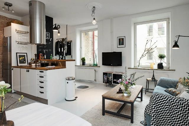 Thiết kế mở từ phòng bếp đến phòng khách và ra phòng ăn tạo cảm giác căn hộ trông rộng hơn, trong khi đó những chiếc cửa sổ cao sát trần cho phép ánh sáng tự nhiên tràn vào bên trong căn hộ.