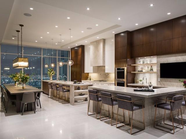 Nhà bếp được thiết kế vô cùng rộng thoáng với rất nhiều chỗ ngồi. Mặt bàn bếp được làm bằng đá cẩm thạch trắng, có đầy đủ tủ lạnh, tủ đông. Ngay cạnh còn có một quầy bar sang trọng có tivi và ghế ngồi.