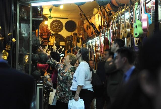 Tổng thống Chile Michelle Bachelet Jeria xem các sản phẩm lưu niệm của Việt Nam (nhạc cụ cổ truyền, tranh sơn mài, lụa...) trên phố Hàng Gai, Hà Nội.