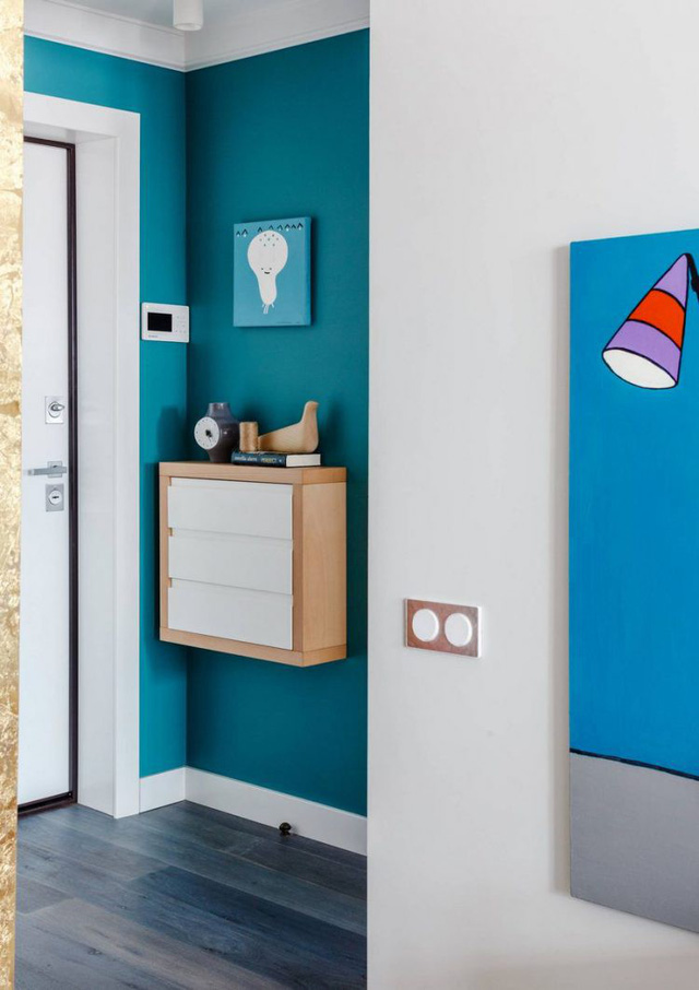 Ngay lối vào nhà, bức tường được sơn màu xanh mát mắt làm nổi bật các gam màu của phụ kiện và vật dụng. Hai bên lối vào được bố trí với tủ đựng giày, giá treo quần áo tiện dụng, giương và nhiều đồ vật dụng trang trí khác.