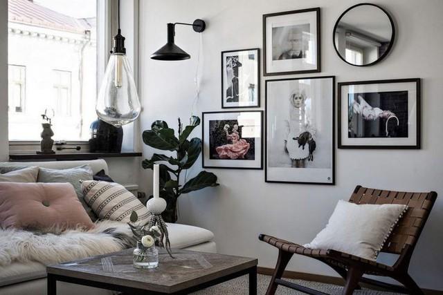 Không gian phòng khách không rộng nhưng rất lôi kéo có dao động tường gạch ghi xám được tô điểm bằng rất nhiều bức tranh treo tường tuyệt đẹp.