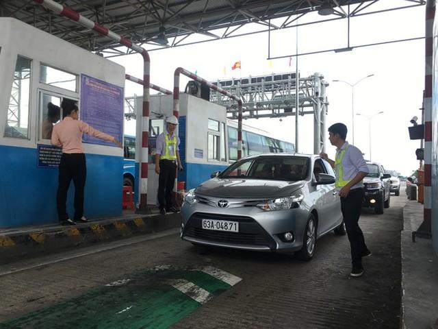 Nhân viên thay phiên bán vé cho tài xế qua trạm.