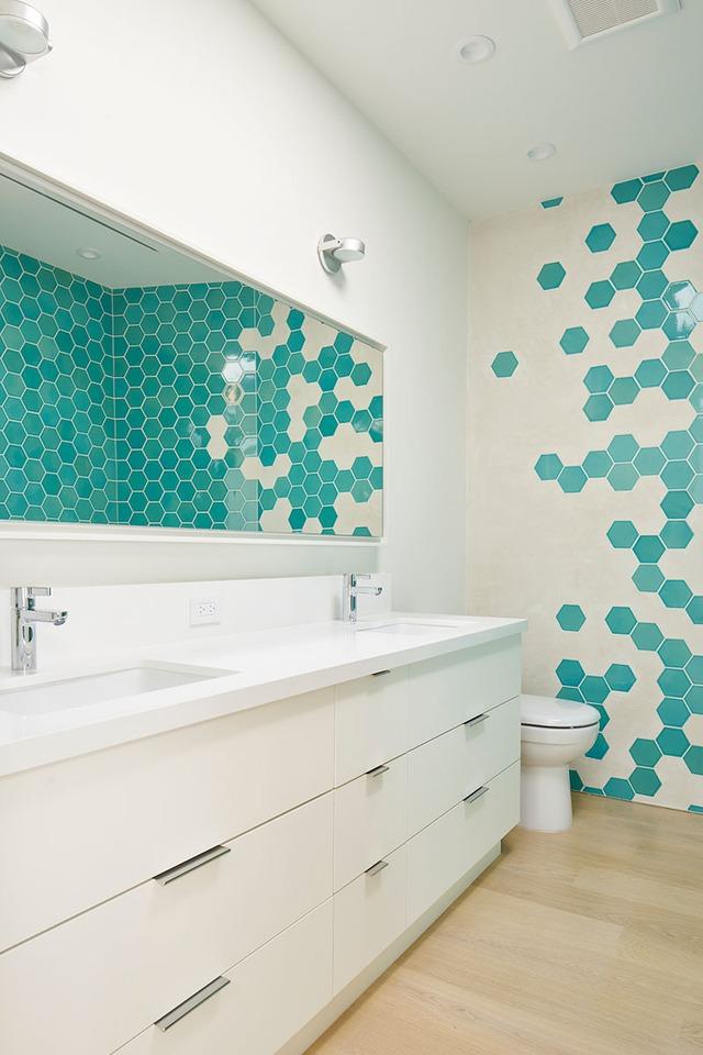 Khu vệ sinh nổi bật với những hình lục giác màu xanh mát mắt.